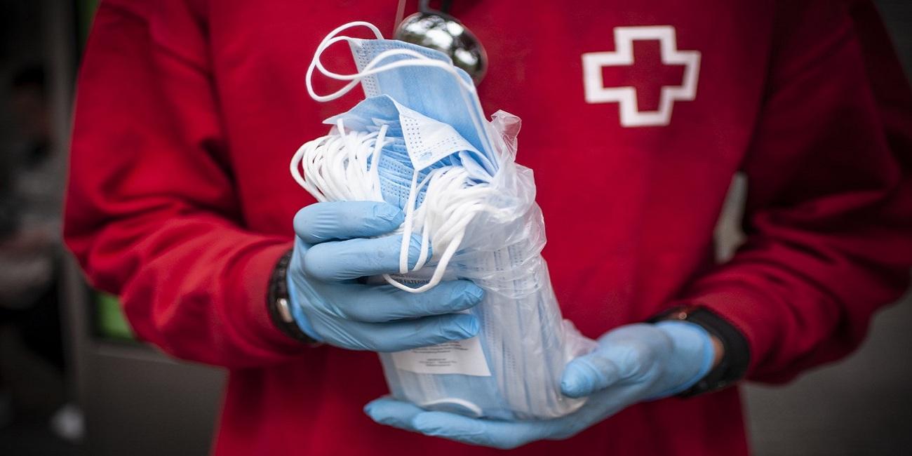Voluntario de Cruz Roja repartiendo mascarillas. Foto: Cruz Roja.