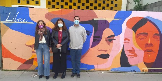 Esther López, Lidia Pozo y Javier Castilla 'Sake' junto al mural pintado en la avenida Padre Villoslada. Foto: TV Baena.