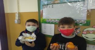 Dos alumnos del colegio Juan Alfonso de Baena con sus piezas de fruta junto al panel del 'Frutómetro'. Foto: CEIP Juan Alfonso de Baena.