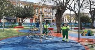 Labores de limpieza y desinfección, esta mañana, en la zona infantil del parque 'Ramón Santaella'. Foto: TV Baena.