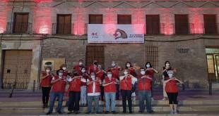 Algunos miembros de la Asamblea Local de Cruz Roja en Baena frente a la Casa del Monte iluminada de rojo. Foto: Cruz Roja.