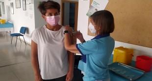 Una mujer recibe la vacuna contra el covid que se están administrando en el pabellón de deportes de Baena. Foto: TV Baena.